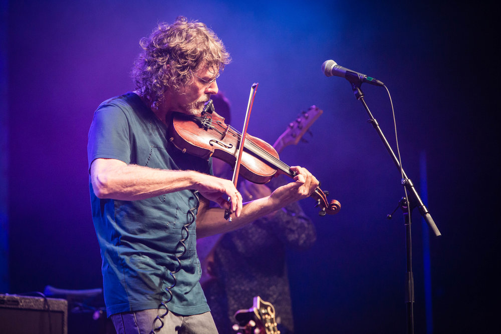 "`<img alt=""Sam Bush playing the Violin on stage""`>"