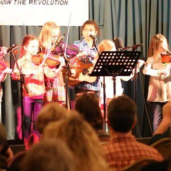 "`<img alt=""Picture of multiple children playing Violin on stage""`>"